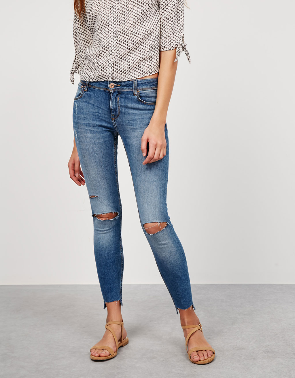 Jeans with asymmetric hem and cut knees