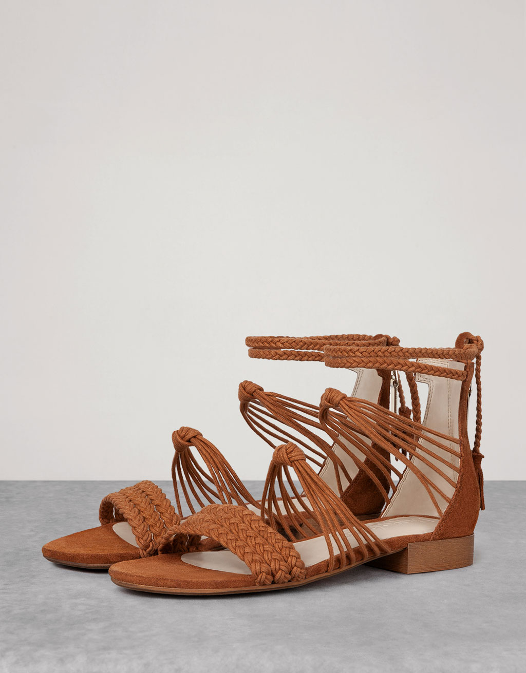 BSK braided flat sandals with pompoms