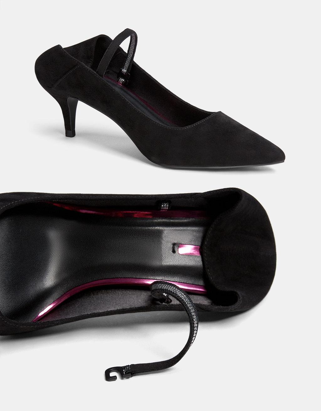 Schuh mit offener Ferse, halbhohem Absatz und Knöchelriemchen.