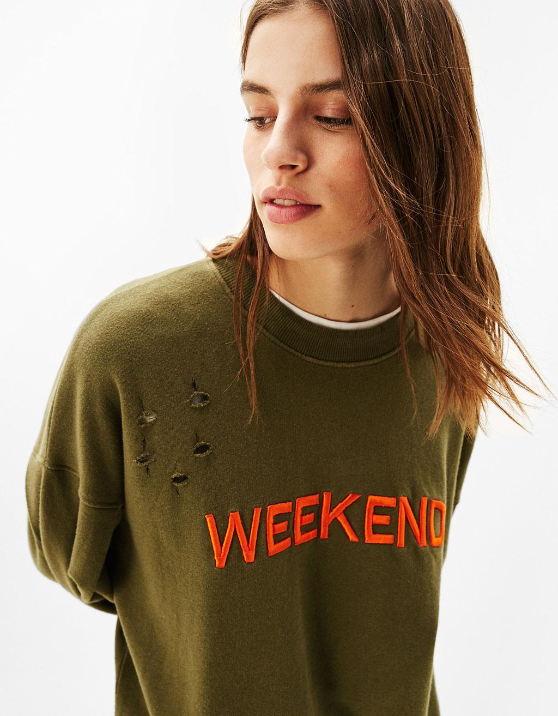 Liels, sportisks džemperis ar platām piedurknēm, plīsumiem un uzrakstu