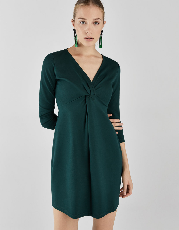 Lyhythelmainen mekko koristesolmulla rinnuksessa