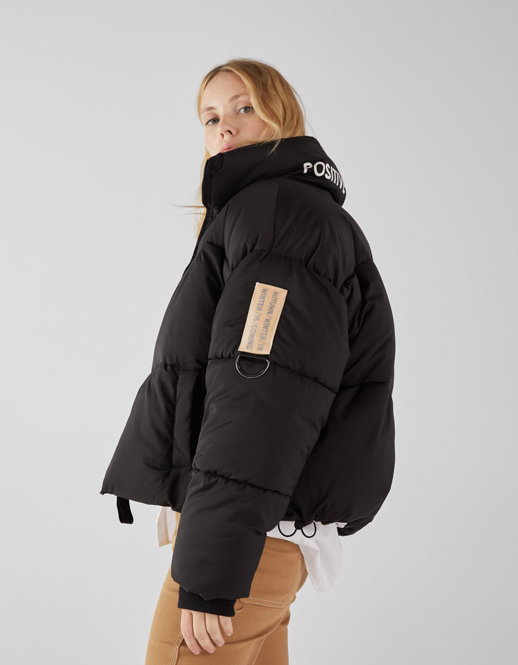 Oversized puffer coat with slogan on the neckline