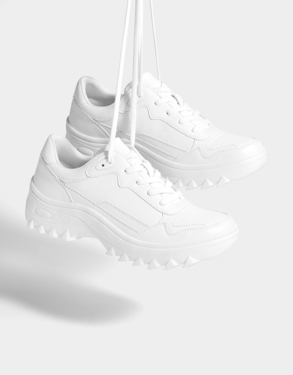 White lace-up sneakers. Topstitching detail on the upper. Chunky sole with studs.