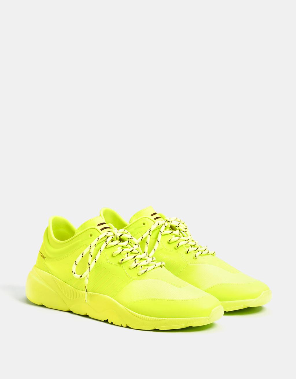 Sneaker di colore giallo fosforescente. Combinazione di materiali tecnici. Suola tecnica gialla.