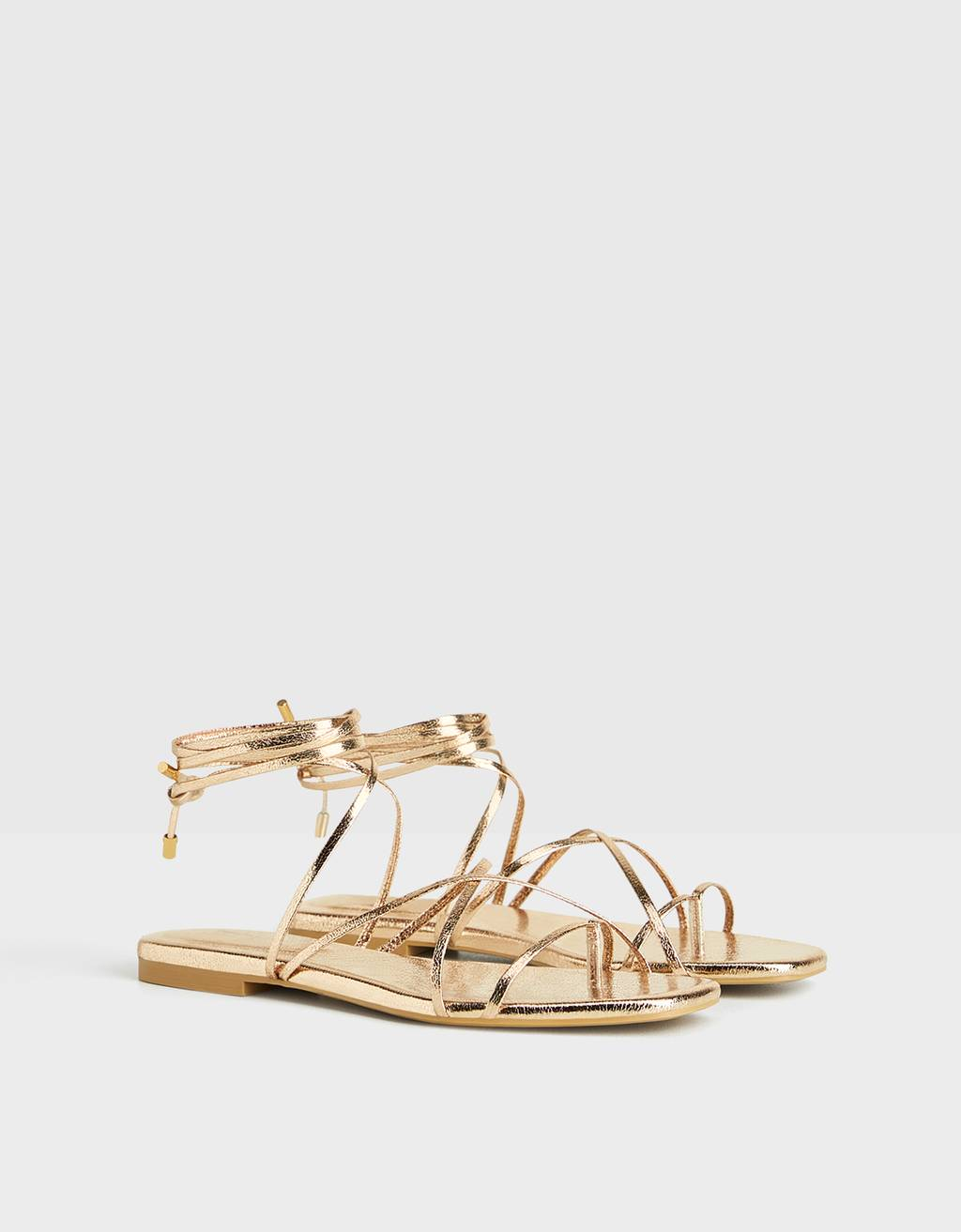 Metallic flat tied sandals.