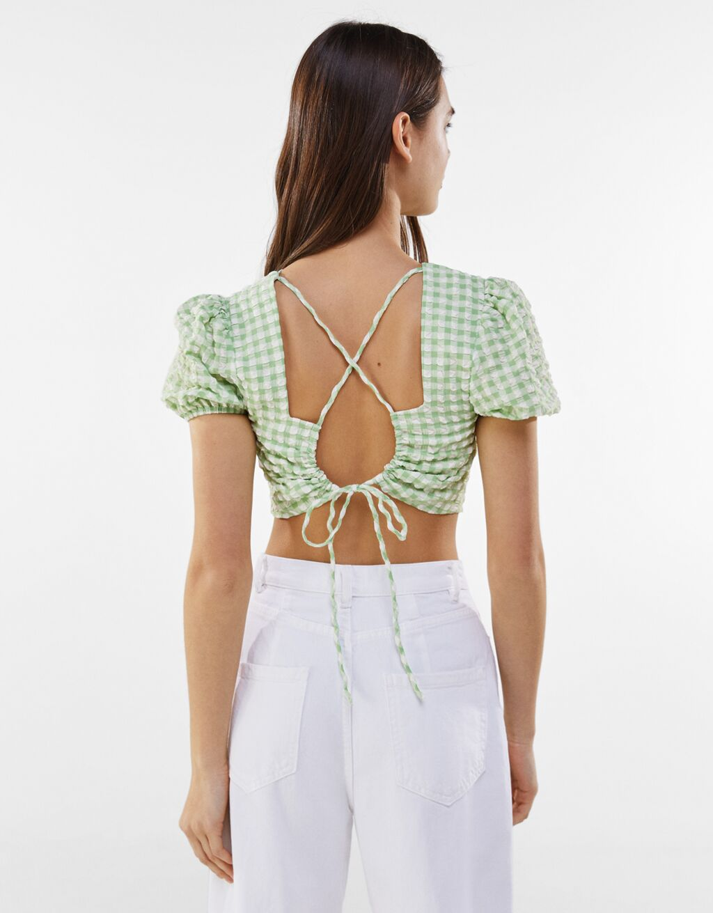 Woman wears Gingham blouse with tied detail at the back and white jeans and faces away from camera